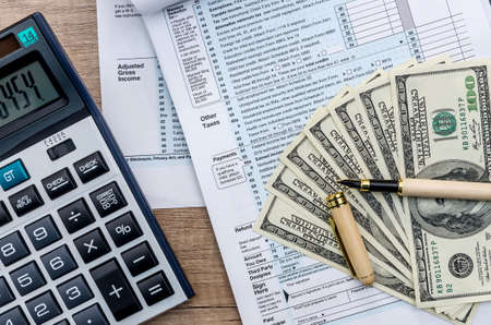 Taxes and savings, tax form with money and calculator