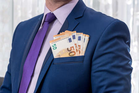 Businessman in suit and euro banknotes in pocket