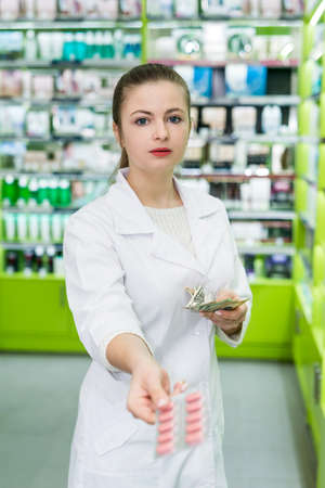 Pharmacist with some pills in blister and dollar notes Foto de archivo