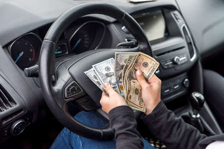 Female hands with dollar banknotes closeup on steering wheel Stock Photo