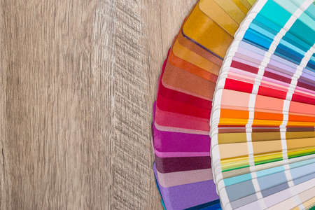 Color swatches in fan on wooden background