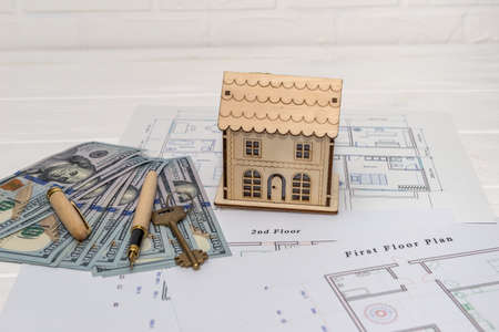 Wooden house model with real key on blueprint