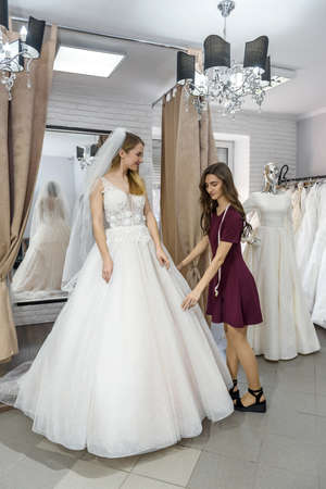 Tailor in wedding salon helping bride to try on dress