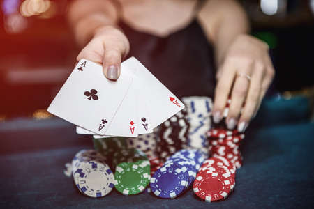Female hands with four aces in casino close up