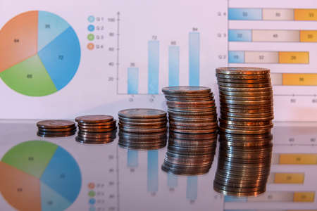 Coins on reflecting surface with business graphs background Stock Photo
