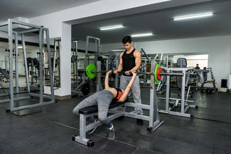Woman in gym working with barbell with instructor's help