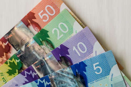 Canadian money. Dollar banknotes on wooden background