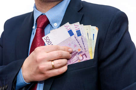 Businessman hands hiding euro banknotes into pocket