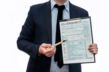 Man in suit showing 1040 tax form on clipboard isolated on white