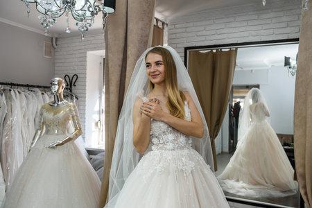 Beautiful bride in wedding dress standing in boutique Zdjęcie Seryjne