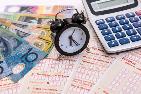 Australian dollars, clock and calculator on tax form Standard-Bild