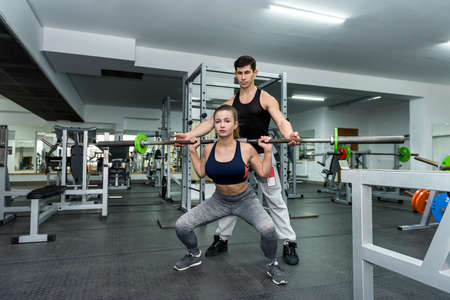 Personal instructor helping woman to lift a dumbbell