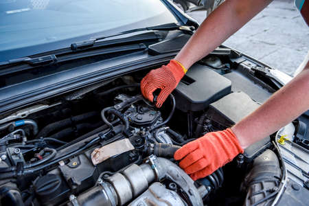 Hands in gloves with car engine close up