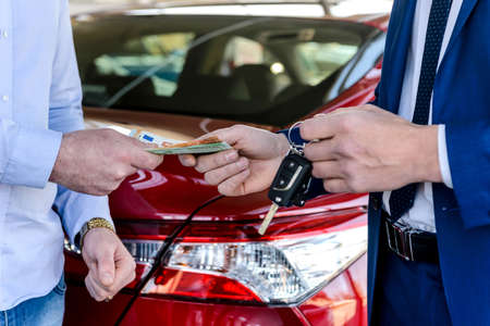 Male hands exchanging with euro and car keys Stock Photo