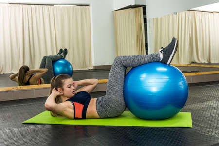 Woman in gym making exercises with big ball