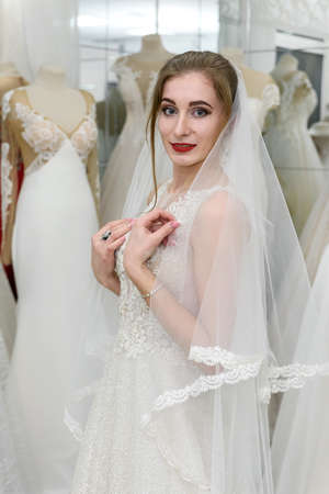 Young woman in wedding dress and veil in bridal shop