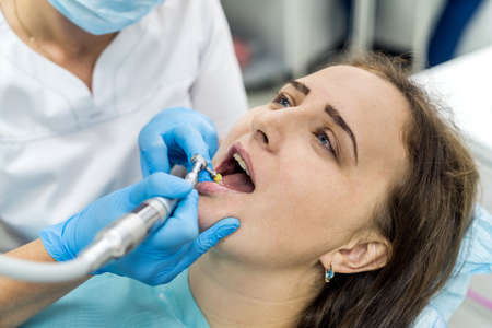 Dentist polishing patient's teeth after whitening procedure Stock Photo
