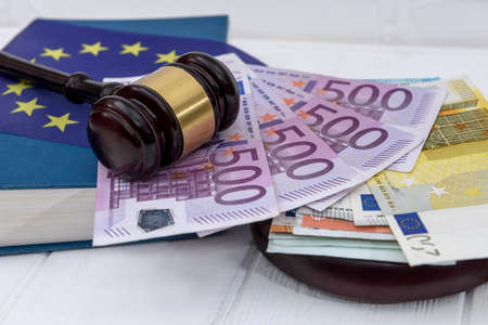 Handcuffs with euro banknotes and judge's gavel Imagens