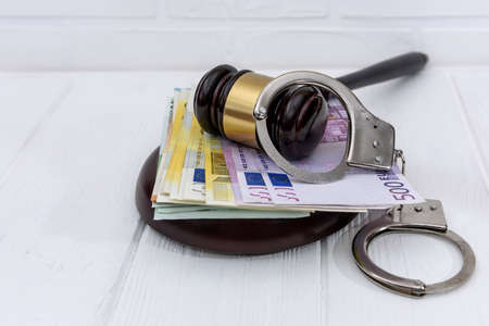 Handcuffs with euro banknotes and judge's gavel