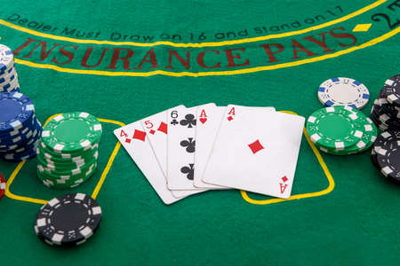 Gambling theme. Colorful casino chips on green poker table close up