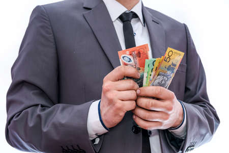 Man in suit counting colorful australian dollars 免版税图像