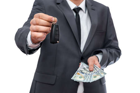 Man in suit holding key from car and dollars