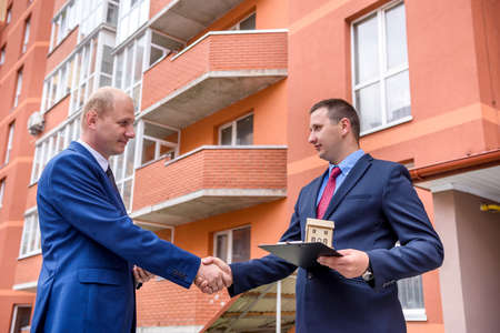 Man signing contract of apartment buy opposite new building