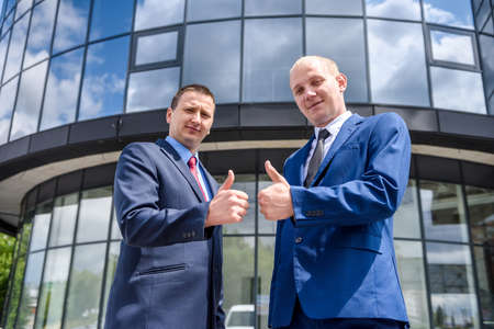 Two men in suits showing thumbs up outdoors