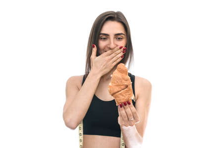Fit woman with croissant isolated on white