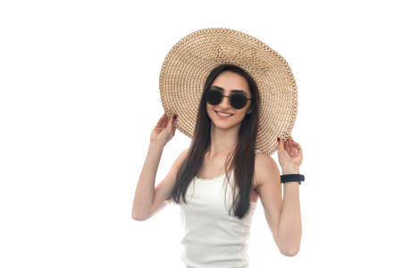 Young woman in hat and sunglasses isolated on white