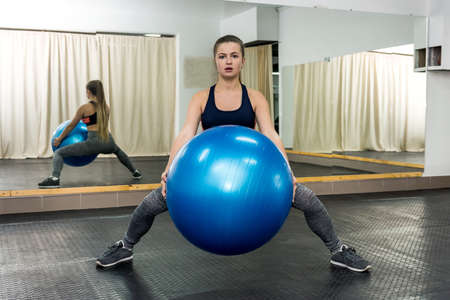 Woman practicing with fitness ball in gym 免版税图像