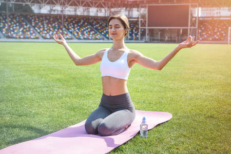 Woman training outdoors. She's sitting on mat on green grass and doing yoga exercises 免版税图像