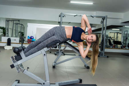 Woman in gym making exercises for belly on equipment