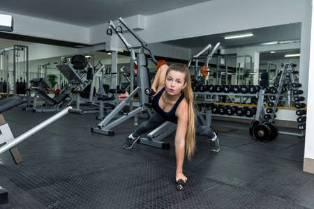 Beautiful woman in gym making plank exercise with dumbbells