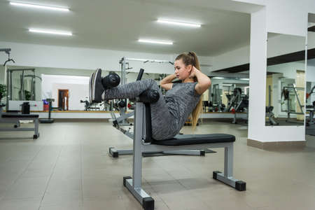 Young woman making torsion exercise in gym