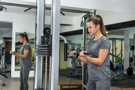 Young woman lifting up barbell in gym