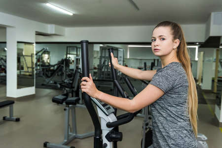 Cycling on exercise bikes. The girl is engaged in exercise bike in the gym