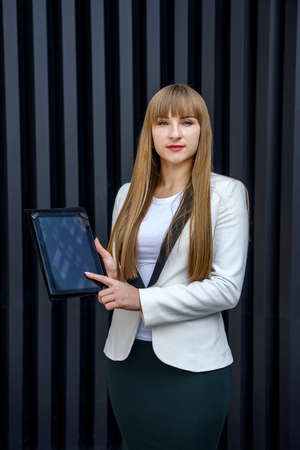 Portrait of young business woman with tablet over gray background