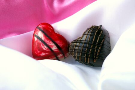 Two Chocolate Hearts on White Satin Stock Photo