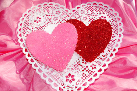pink satin: Pink and Red Glitter Hearts on White Doile and Pink Satin Stock Photo