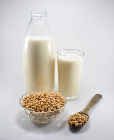 Flasche Milch und Glas mit Sojamilch, Schüssel und Löffel mit Sojabohnen
