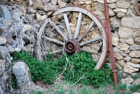 Abandoned wooden cartwheel on the wall. Vintage concept photo