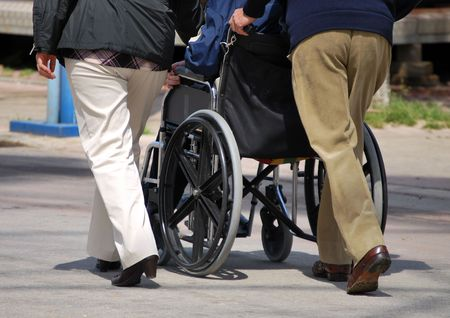 crippled: A family stroll. The child is in a wheelchair