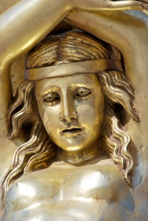 Golden human female face. Antique sculpture photo