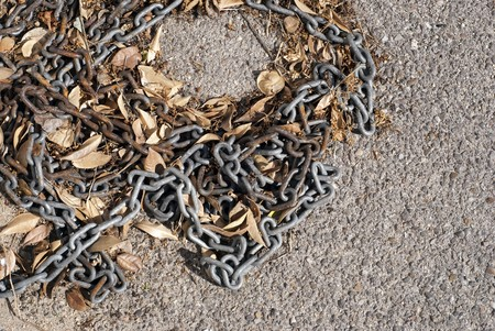 Old and grungy chain on the ground with leafs Stock Photo - 7848720
