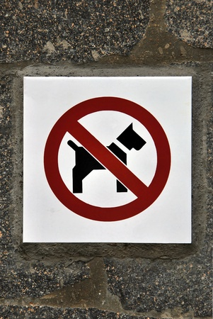 Forbidden dogs sign on a stone wall. photo