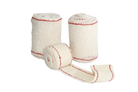 white bandage: some rolls of bandage isolated over white. Medical treatment concept