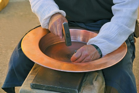 forger: Artisan engraving by hand. An artist is working in a dish of copper