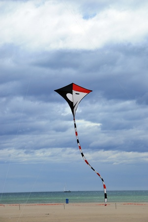 clody sky: A kite is flying over the beach Stock Photo