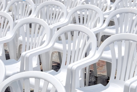disposed: White plastic chairs disposed in rows on the street Stock Photo